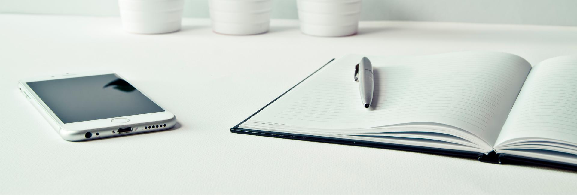 Muistilehtiö ja puhelin pöydällä