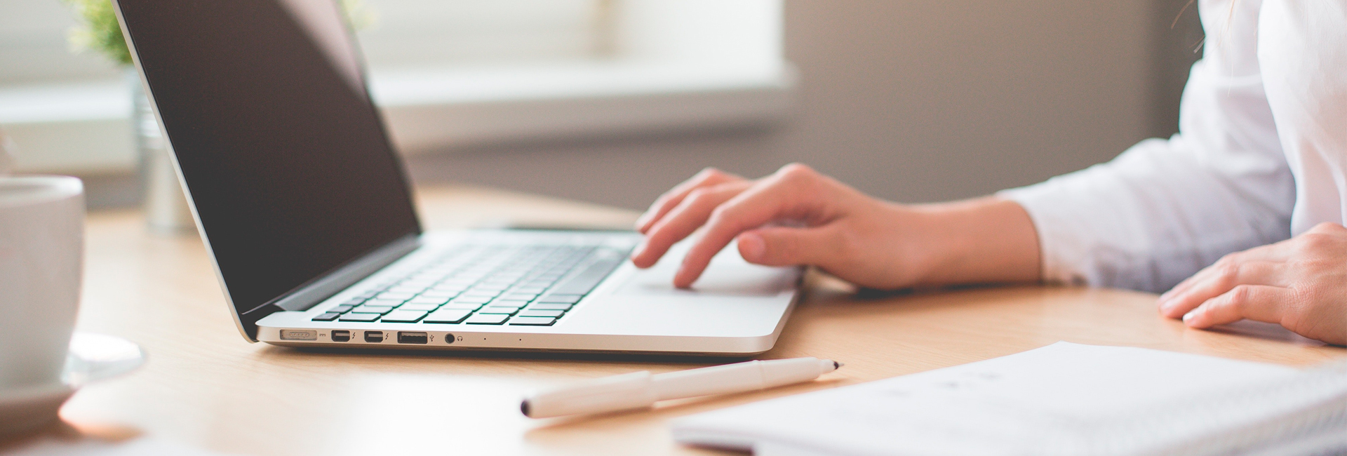 Kauluspaitainen henkilö käyttää kannettavaa tietokonetta